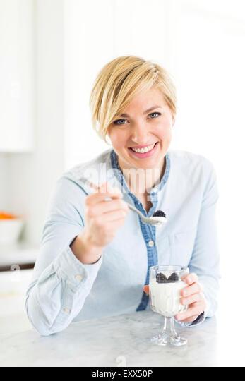 Portrait of woman eating yogurt with blackberries - Stock Image