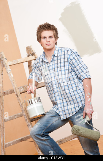 Home improvement: Young man with paint roller, paint can and ladder - Stock Image