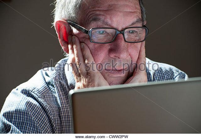 Older man using laptop computer - Stock Image