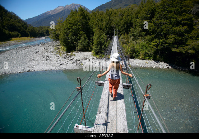 Girl on hanging bridge, track to Blue Pools, east of  Haast Pass, Southern Alps, South Island, New Zealand - Stock-Bilder
