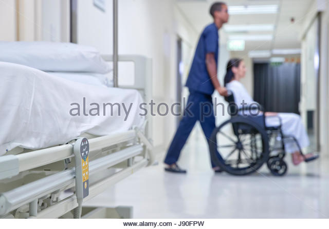 Male Nurse Pushing Patient Along Hospital Corridor In Wheelchair - Stock-Bilder