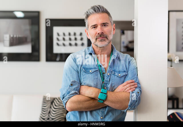 Caucasian man with arms crossed leaning on pillar - Stock-Bilder