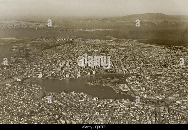 historical aerial photograph of Lake Merritt and downtown Oakland, California with San Francisco and the Golden - Stock Image