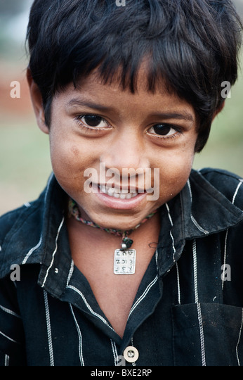 Young poor lower caste Indian street boy smiling - Stock Image