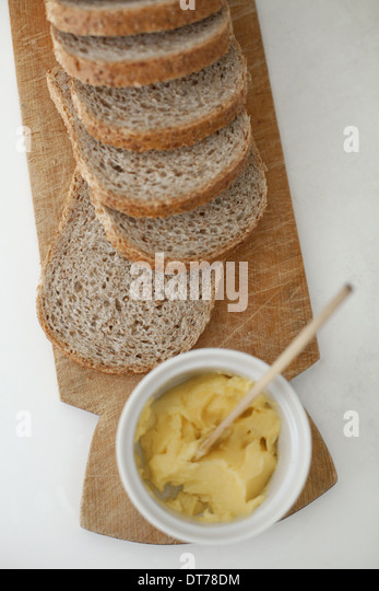 A wooden breadboard with a sliced brown loaf laid out. A dish of butter with a wooden butter knife. - Stock Image