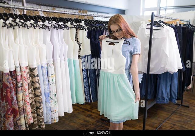 Woman selecting a dress - Stock Image