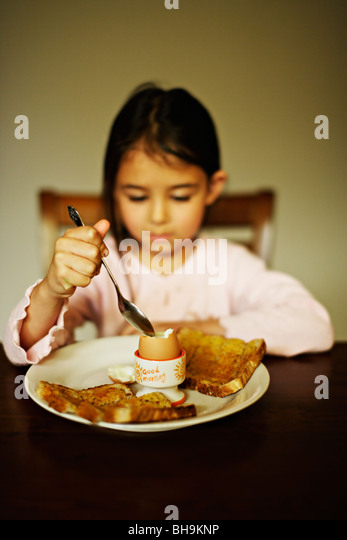 Five year old girl eats boiled egg for breakfast - Stock Image
