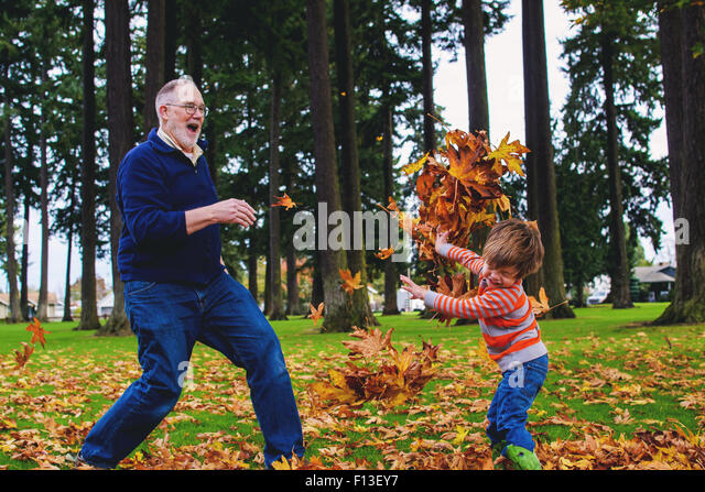 Boy throwing leaves at his grandfather - Stock Image