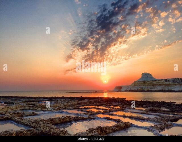 Sunrise over actively harvested salt pans - Stock Image