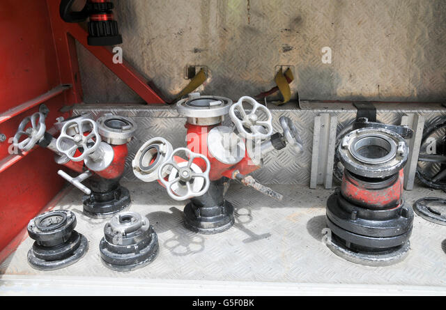 Fire fighters equipment hoses on a rack - Stock Image