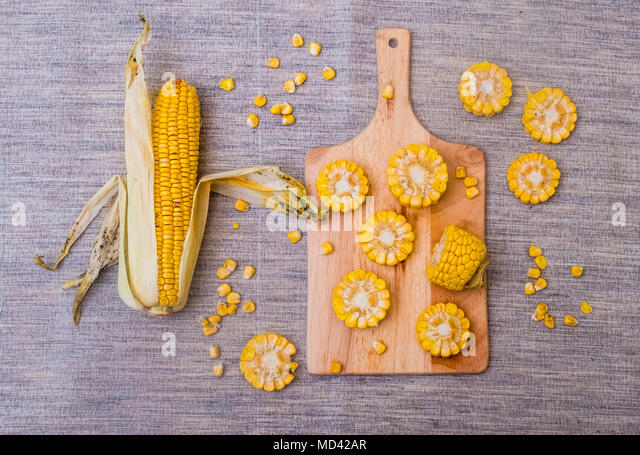 Sliced corn on the cob on chopping board, overhead view - Stock Image