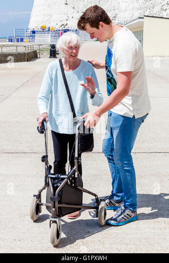 Smiling carer pushing an old man in a wheelchair stock photo image - Carer Uk Stock Photos Amp Carer Uk Stock Images Alamy
