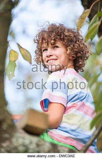 Boy sitting on tree - Stock Image