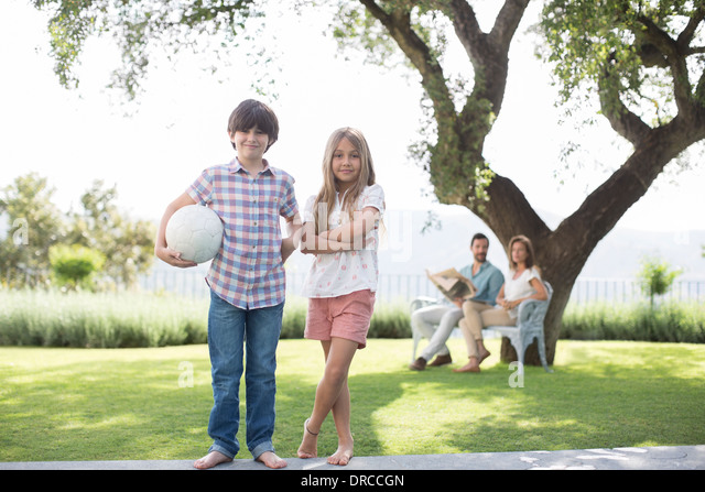 Brother and sister with volleyball in backyard - Stock Image