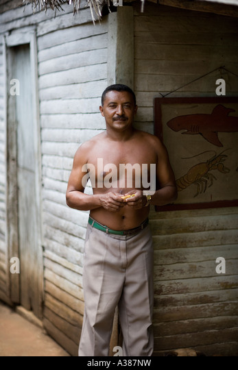A Cuban man stands outside his wooden house in Cuba s Guantanamo province - Stock Image