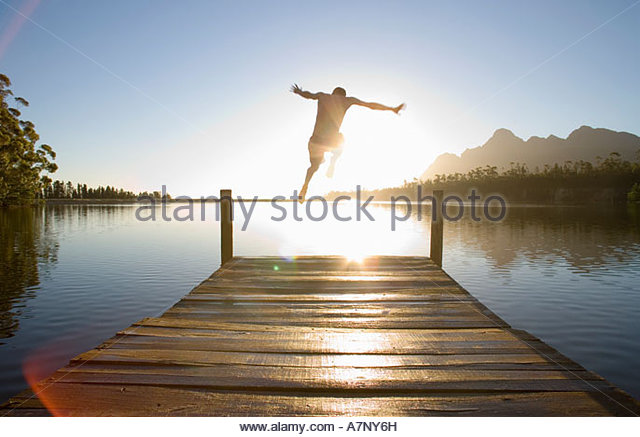 Man jumping from jetty into lake at sunset rear view lens flare backlit - Stock Image