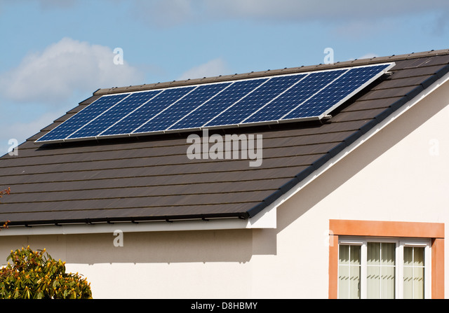 Photovoltaic Solar panels Mounted on a new tile roof of a modern home - Stock Image