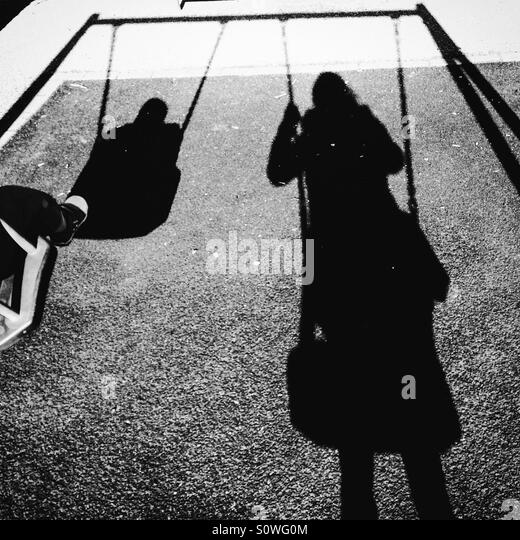 Shadow of Mum and toddler on swings - Stock-Bilder