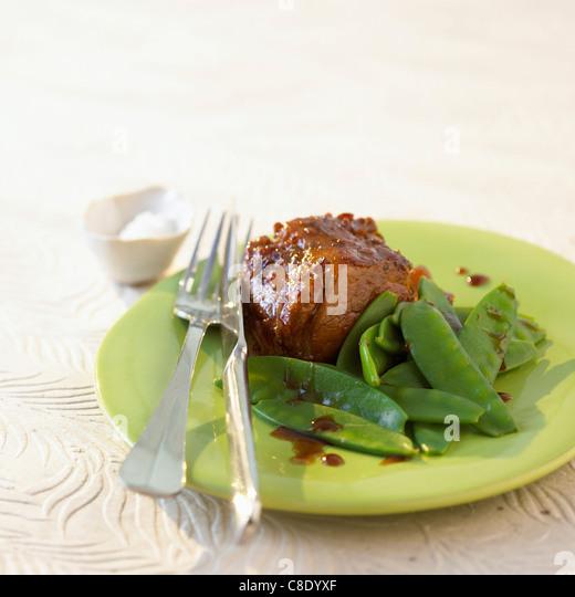 Pork filet mignon with sugar peas - Stock Image