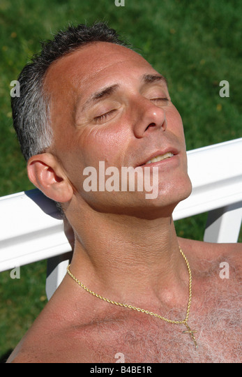 Closeup Portrait of a Man Soaking in the Sun He is Leaning Against a White Rail - Stock Image