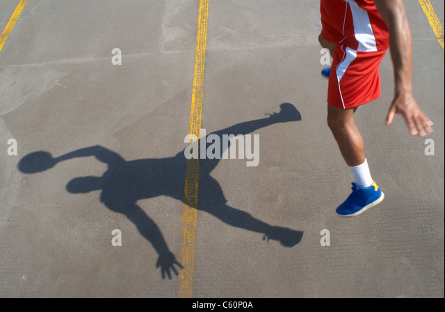 Basketball player jumping with ball - Stock Image