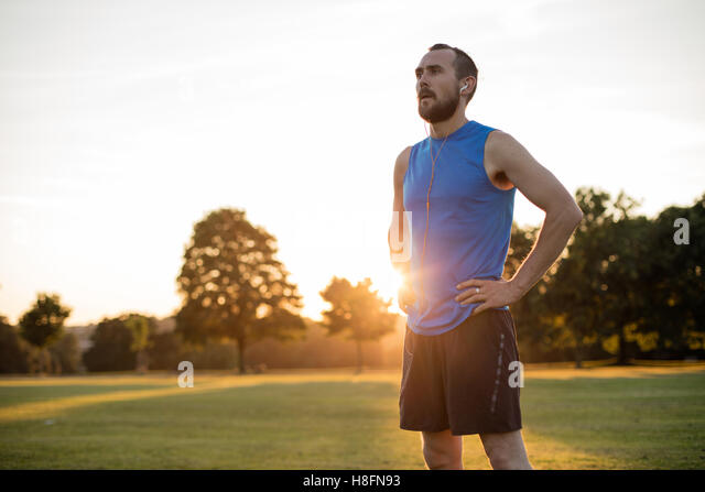 Young athletic man resting after a run in the park while the sun sets - Stock-Bilder