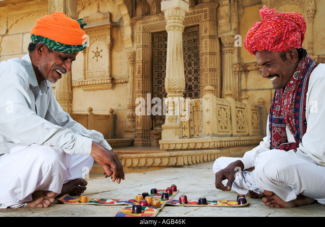 Two men playing a traditional Hindu game Chopar in front of the Siva Temple at Gadisar Lake - Stock Image