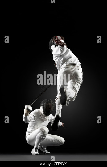 Fencers fencing, one fencer jumping in air - Stock Image
