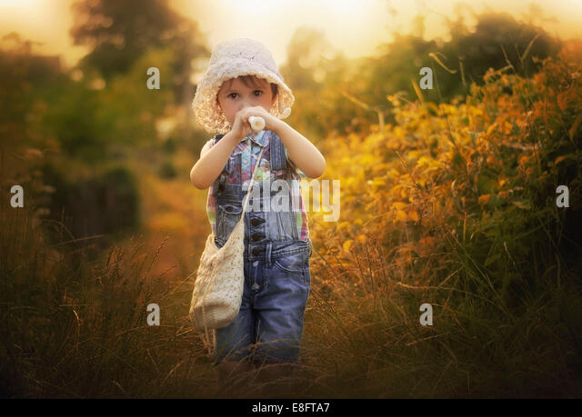 Girl outdoors playing recorder - Stock Image