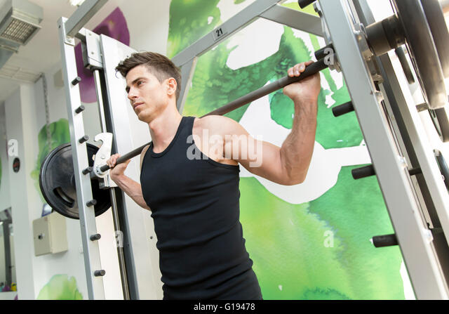 Handsome man training in gym to stay fit and strong - Stock Image