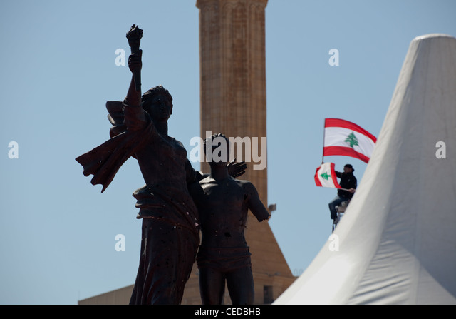 Silhouette of Martyrs Square statue in the city centre of Beirut, Lebanon. A figure holds a Lebanese flag. - Stock Image
