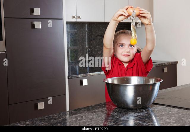 Girl cracking egg over bowl - Stock Image