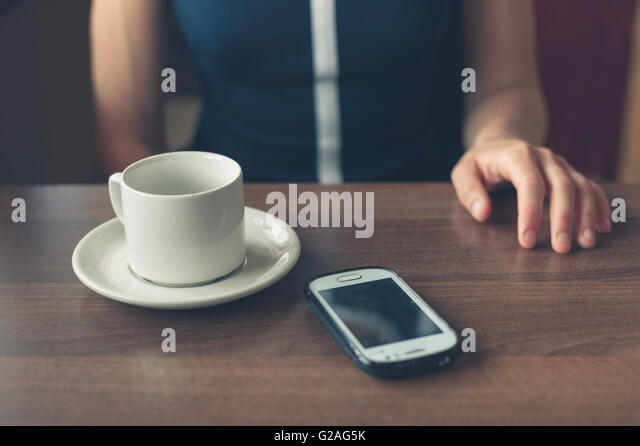 A young woman is sitting by the window in a diner with a cup and a smartphone in front of her - Stock Image