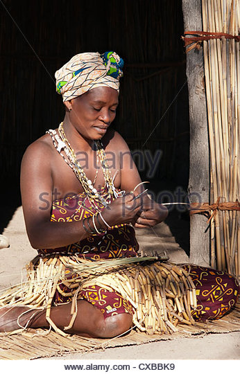 Woman weaving reeds to create a basket, Kxoe village, Kwando river area, Caprivi Strip, eastern Namibia, Africa - Stock Image