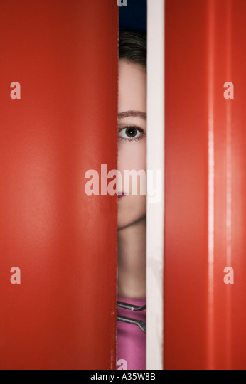 Woman Behind Secured Door Looking Out Of Apartment - Stock-Bilder