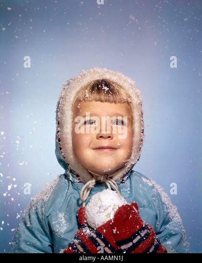 1960s LITTLE GIRL HOLDING SNOW BALL LOOKING UP AT SKY SMILING RED MITTENS WHITE KNIT HAT BLUE JACKET RETRO - Stock Image
