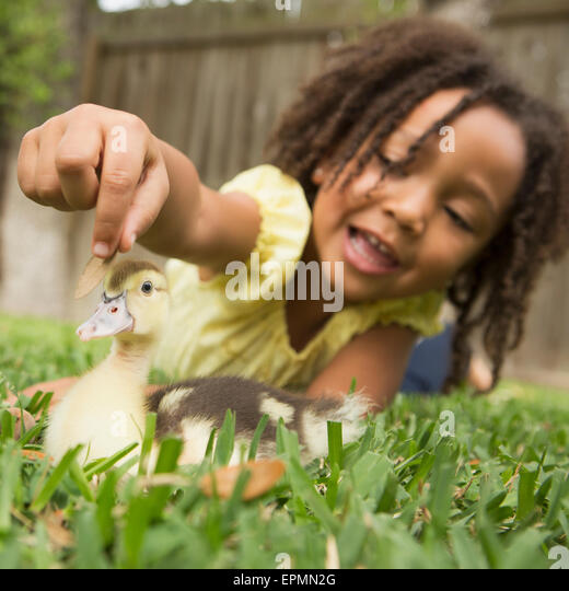 A young girl lying on the grass stroking the head of a duckling. - Stock Image