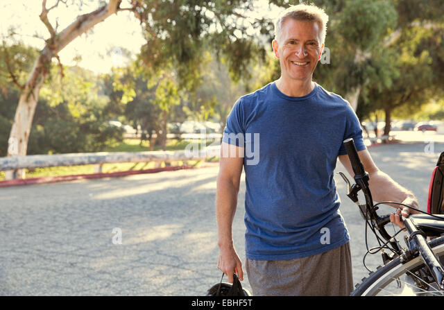 Portrait of mature male cyclist in park - Stock Image