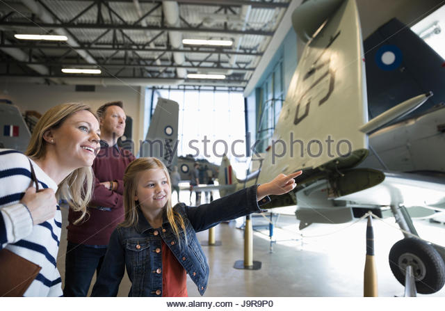 Curious family pointing at airplane in war museum hangar - Stock-Bilder