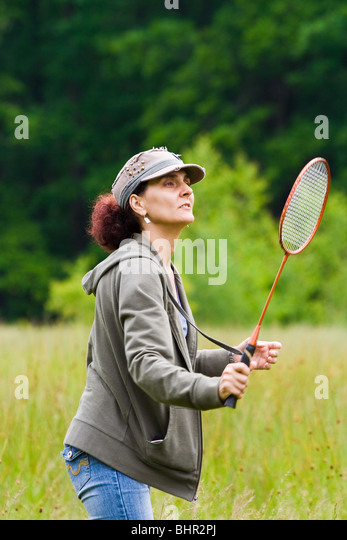 Woman with cap playing badminton in a meadow - Stock Image