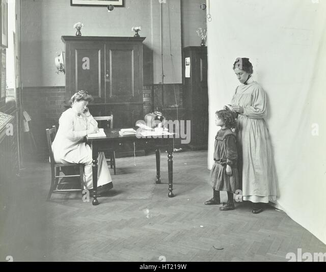School nurse examining girls' hair for head lice, Chaucer School, London, 1911. Artist: Unknown. - Stock Image