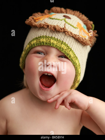 Baby girl in lion hat - Stock Image