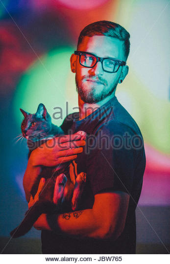 Portrait of young man holding pet cat, against colourful studio background - Stock-Bilder