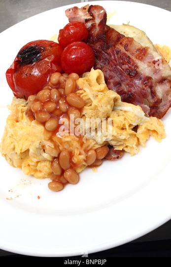 Individual portion of scrambled eggs baked beans bacon tomatoes - Stock Image