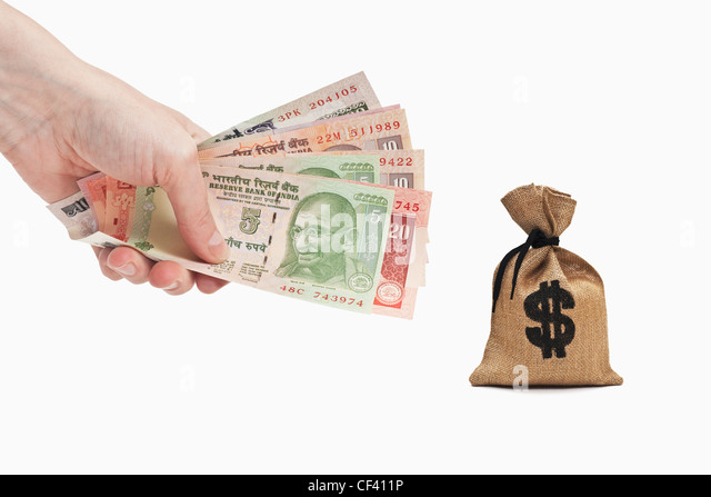 Many diverse Indian rupee bills are held in the hand. Near by is a money bag with a U.S. Dollar currency sign. - Stock-Bilder