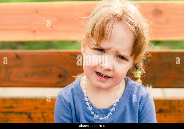 Lifestyle portrait of a young girl at a park with natural light. - Stock Image