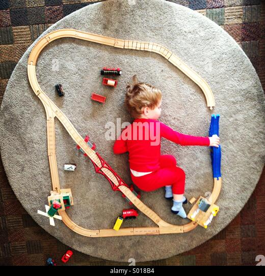 Little boy playing with a toy train track - Stock Image