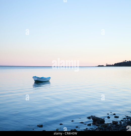Small rowing boat anchored on gently lapping water - Stock Image