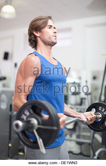 Man lifting barbell in gymnasium - Stock Image