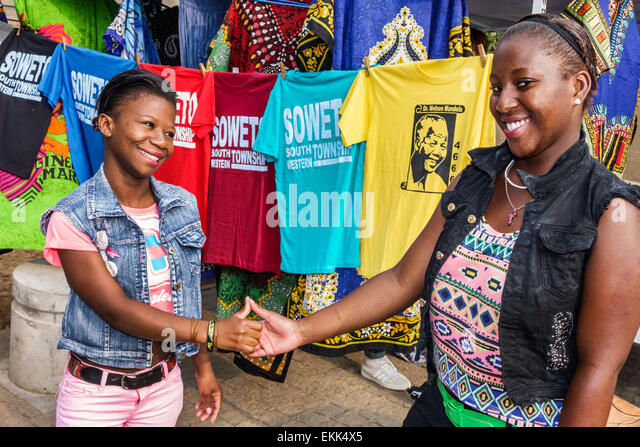 South Africa African Johannesburg Soweto Vilakazi Street Precinct Black woman friends vendors souvenir greet greeting - Stock Image